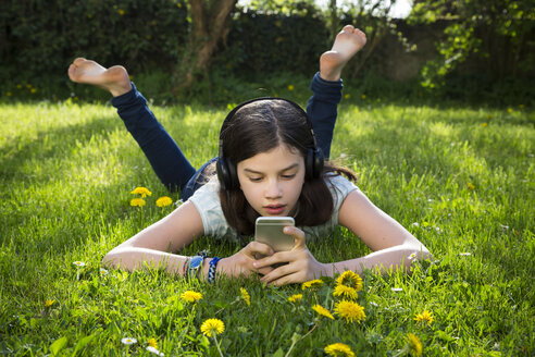 Girl lying on meadow listening music with headphones using smartphone - LVF06935