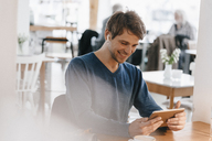 Smiling man in a cafe with earphone using tablet - KNSF03837