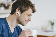 Smiling man in a cafe with earphone drinking coffee - KNSF03843