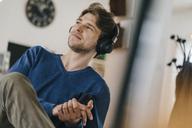 Smiling man in a cafe wearing headphones - KNSF03846