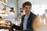 Smiling man in a cafe holding cup - KNSF03852