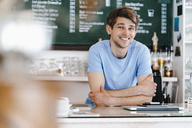 Portrait of smiling man in a cafe - KNSF03855