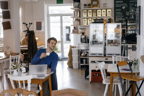 Man sitting at table in a cafe with laptop - KNSF03870