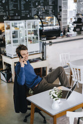 Smiling man in a cafe with laptop on cell phone - KNSF03876