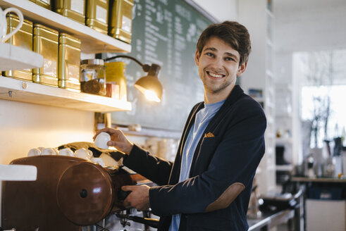 Portrait of smiling man in a cafe holding cup - KNSF03885