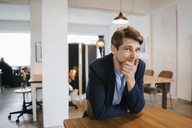 Portrait of smiling man sitting at table - KNSF03897