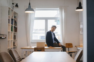 Portrait of smiling man sitting on table with laptop - KNSF03903