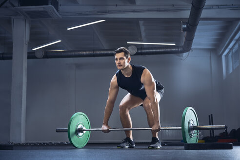 Man doing barbell exercise at gym during weight lifting workout - BSZF00311