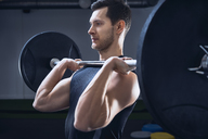 Man doing push press barbell exercise at gym - BSZF00314