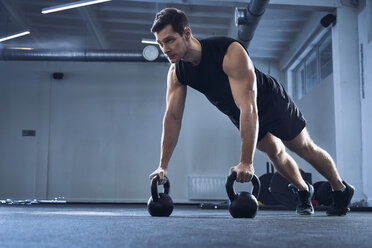 Man doing pushups on kettlebells at gym - BSZF00320