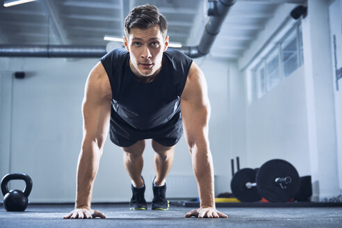 Athletic man doing pushups exercise at gym - BSZF00323