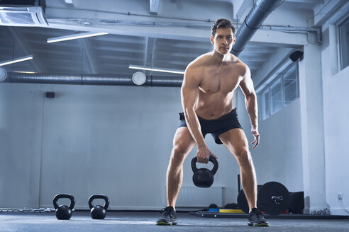 Athletic man doing kettlebell swing exercise at gym - BSZF00326