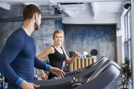 Man and woman talking during treadmill exercise at gym - BSZF00329