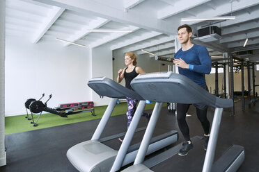 Man and woman running on treadmill at gym - BSZF00332