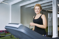 Portrait of smiling woman on treadmill at gym - BSZF00335