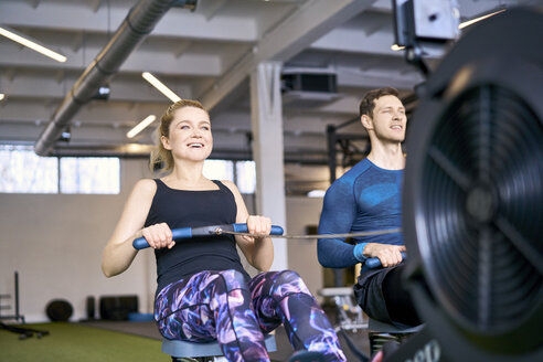 Man and woman at gym exercising together on rowing machines - BSZF00338