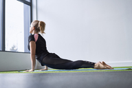 Woman doing yoga exercise in studio - BSZF00344