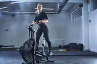 Athletic woman doing air bike workout at gym - BSZF00347