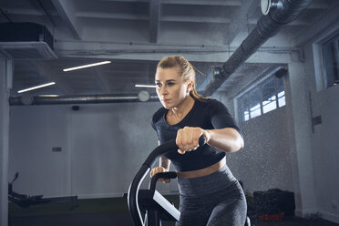 Athletic woman doing air bike workout at gym - BSZF00350
