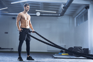 Athletic man exercising with battle ropes at gym - BSZF00353