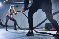 Athletic woman doing battlerope exercise with personal trainer at gym - BSZF00356