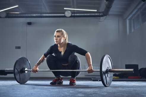 Woman doing barbell exercise at gym during weight lifting workout - BSZF00362