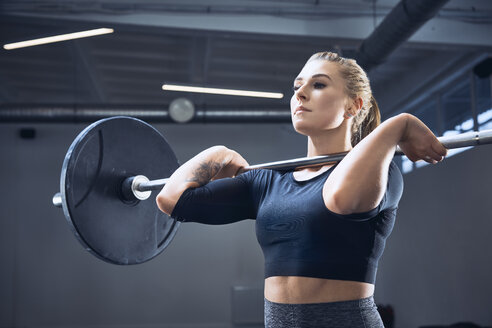 Woman doing push press exercise at gym - BSZF00365