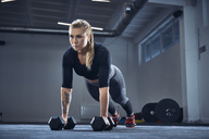 Woman practicing dumbbell push-up exercise at gym - BSZF00368