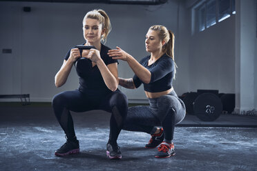 Woman practicing kettlebell squat with personal trainer at gym - BSZF00371