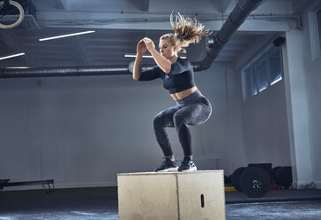 Athletic woman doing box jump exercise at gym - BSZF00374