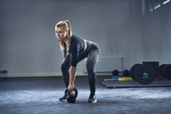 Woman exercising with kettlebell at gym - BSZF00377