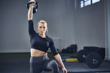 Woman doing kettlebell exercise at gym - BSZF00380