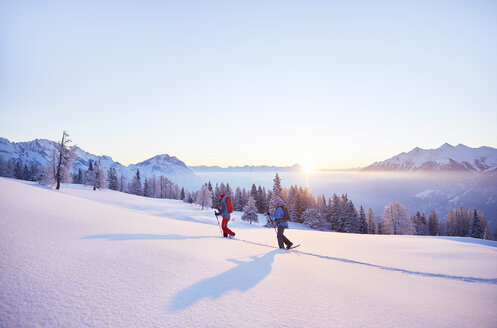 Austria, Tyrol, snowshoe hikers at sunrise - CVF00404