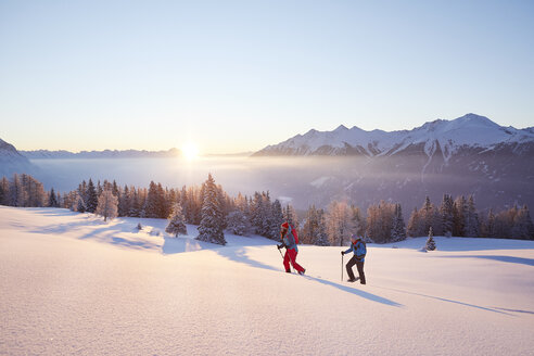 Austria, Tyrol, snowshoe hikers at sunrise - CVF00410