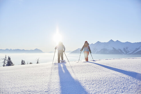 Austria, Tyrol, snowshoe hikers at sunrise - CVF00413