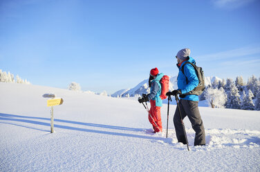 Austria, Tyrol, couple snowshoeing, standing in front of sign post - CVF00416