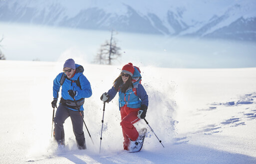 Austria, Tyrol, snowshoe hikers running through snow - CVF00419