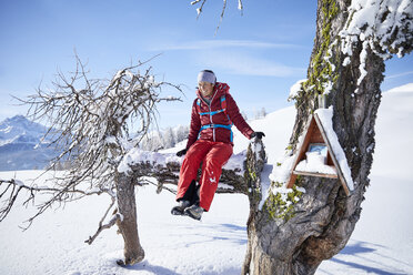Austria, Tyrol, female hiker sitting on branch - CVF00437