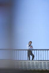 Businesswoman standing on bridge against blue sky using smartphone - BEF00027