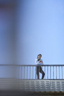 Businesswoman standing on bridge against blue sky using smartphone - BEF00027
