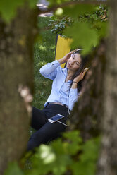 Young woman sitting on a meadow listening music with headphones and cell phone - BEF00033