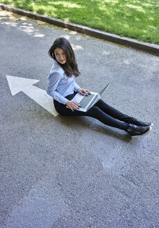 Young woman with laptop sitting on arrow sign on street - BEF00036