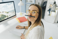 Portrait of funny young woman at desk pouting mouth - GUSF00744