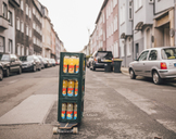 Stack of three boxes with lemonade bottles standing on longboard on the street - GUSF00747
