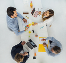 Four business people at meeting table in office, top view - GUSF00753