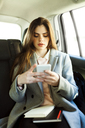 Portrait of young businesswoman sitting on backseat of a car looking at cell phone - VABF01567
