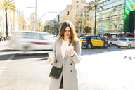 Spain, Barcelona, young woman with coffee to go standing at roadside looking at cell phone - VABF01579