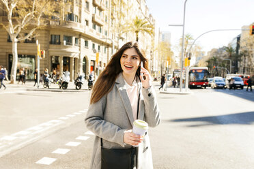 Spain, Barcelona, portrait of smiling young woman on the phone standing at roadside - VABF01582