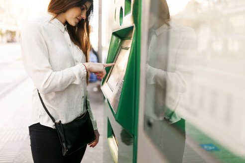 Spain, Barcelona, woman buying ticket from automated machine at  station - VABF01591