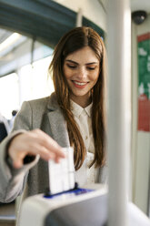 Portrait of smiling young woman validating ticket in tramway - VABF01594